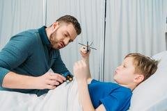 在医院生使用与在医院病床、爸爸和儿子上的病的小男孩 免版税库存照片