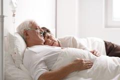 在医院病床上的资深夫妇 免版税库存图片