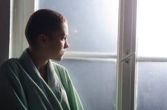 在医院窗口前面的年轻沮丧的癌症患者 库存图片