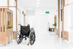 在医院走廊停放的空的轮椅 图库摄影