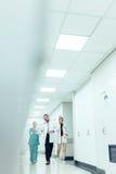 在医院走廊的谈论的医疗队工作 免版税库存照片