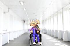 在医院轮椅的资深夫妇 库存照片