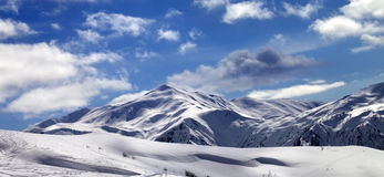 在滑雪倾斜和美丽的天空的全景与在太阳的云彩 免版税库存图片