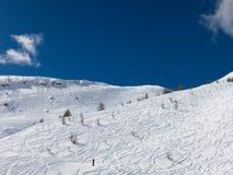在滑雪倾斜的白色曲线和与云彩的蓝天 库存图片