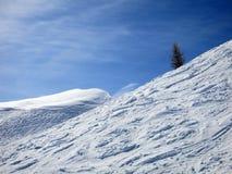 在滑雪倾斜的白色曲线和与云彩的蓝天 免版税库存照片