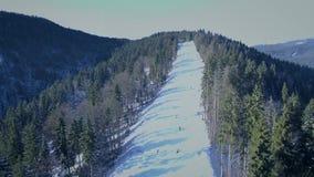 在滑雪倾斜的飞行在滑雪胜地Bukovel,喀尔巴阡山脉,乌克兰 4K空中寄生虫视图 影视素材