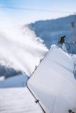 在滑雪倾斜的Snowmaker喷洒的水 免版税库存图片