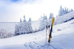 在滑雪坡道的滑雪设备与在雪盖的杉木森林 免版税库存图片