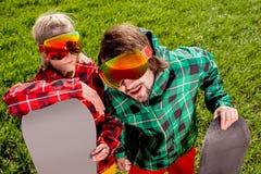 在滑雪服和太阳镜的夫妇看一看滑稽的对来了 免版税图库摄影