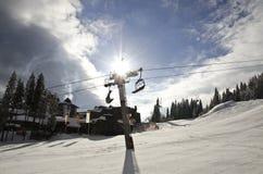 在滑雪电缆车杆后的太阳射线 免版税库存照片