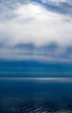 在水面上的云彩的太阳光芒 免版税库存照片