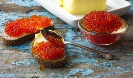 在黑面包的红色鱼子酱用黄油 健康的食物 鱼开胃菜 老蓝色农村木背景 免版税库存照片