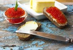 在黑面包的红色鱼子酱用黄油 健康的食物 鱼开胃菜 老蓝色农村木背景 库存照片
