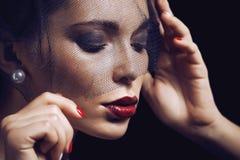 在黑面纱下的秀丽深色的妇女与红色 免版税库存图片