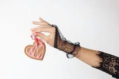 在黑鞋带手套的一只美好的女性手拿着在红色丝带的一个心形的姜饼曲奇饼 库存照片
