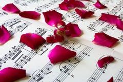 在活页乐谱的玫瑰花瓣 免版税库存图片