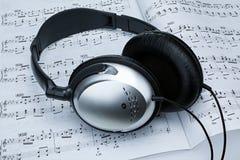 在活页乐谱的银色耳机 免版税库存图片