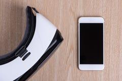 在头顶上虚拟现实耳机和智能手机平展被放置的看法  免版税库存照片