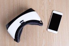在头顶上虚拟现实耳机和智能手机平展被放置的看法  库存图片