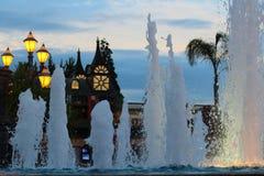 在主题乐园的喷泉由暮色天空 库存照片