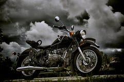 在暴风云下的葡萄酒摩托车 免版税库存图片