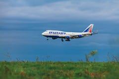 在暴风云背景的波音747-400 Transaero航空公司  免版税库存照片