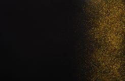 在黑,抽象背景的金黄闪烁沙子纹理边界 免版税库存图片