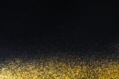 在黑,抽象背景的金黄闪烁沙子纹理边界 免版税库存照片