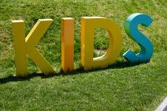 在3D做的题字孩子形成在绿草的身分 免版税库存照片