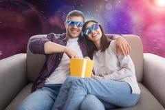 在3D玻璃的夫妇坐长沙发和手表电视 免版税库存图片