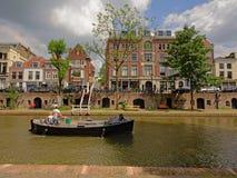 在` oudegracht `运河的休闲小船在乌得勒支,有典型的荷兰房子的,当地窖出来在一个老码头 免版税库存照片