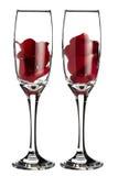 在2块香槟玻璃里面的红色玫瑰花瓣 免版税库存照片
