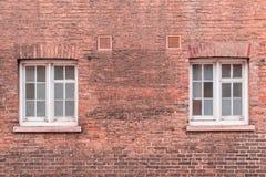 在a被恢复的红砖墙壁上的两扇白色木上下开关窗  免版税库存照片