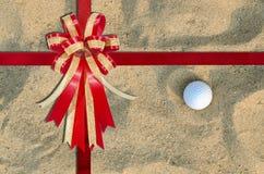 在A高尔夫球的红色丝带在背景的沙子 库存图片