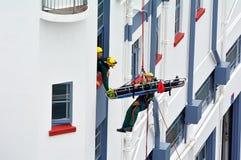 在abseiling的伤害期间的消防队员撤出锻炼 免版税库存图片