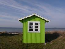 在Aeroe丹麦海岛上的鲜绿色的海滩小屋有海和蓝色sk的背景 图库摄影
