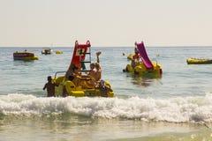 在Albuf使职员和假日制造者靠岸在被聘用的Pedalos战斗与接踵而来的海浪出去入更加镇静的水在海滩 免版税库存照片