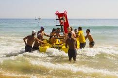 在Albuf使职员和假日制造者靠岸在被聘用的Pedalos战斗与接踵而来的海浪出去入更加镇静的水在海滩 库存照片