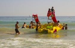 在Albuf使职员和假日制造者靠岸在被聘用的Pedalos战斗与接踵而来的海浪出去入更加镇静的水在海滩 免版税库存图片