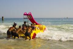 在Albuf使职员和假日制造者靠岸在被聘用的Pedalos战斗与接踵而来的海浪出去入更加镇静的水在海滩 库存图片