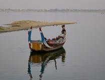 在Amarapura湖的一条小船Ubein桥梁的 图库摄影