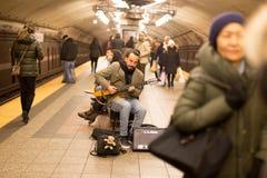 在ampfire的商标立方体-在纽约供以人员弹在地下火车站的吉他 免版税库存图片