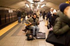 在ampfire的商标立方体-在纽约供以人员弹在地下火车站的吉他 库存图片
