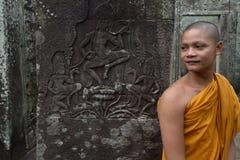 在Apsara舞蹈家石雕刻前面的和尚 库存照片
