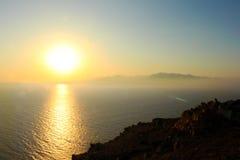 在Armenistis灯塔的日落在米科诺斯岛,希腊 免版税库存照片