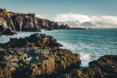 在Arnarstapi地区的典型的冰岛日出日落峭壁风景在Snaefellsnes半岛在冰岛 免版税库存照片
