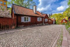 在Asoberget的狭窄的铺有鹅卵石的街道与在falun房屋涂料典型的木住宅红色和与白色快门  免版税图库摄影