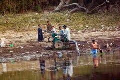 在Aswnm附近的里约Nilo,埃及, 2017年2月21日:工作在马达泵和清洗它的成人和孩子给thei带来水 免版税库存图片