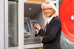在ATM旁边的Bussines妇女 图库摄影