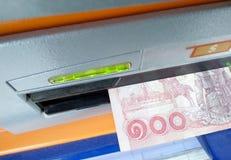 在ATM机器的金钱槽孔的泰国巴恩现金 图库摄影